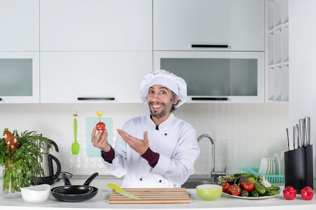 Vooraanzicht blije mannelijke chef-kok in uniform die tomaat in de keuken vasthoudt