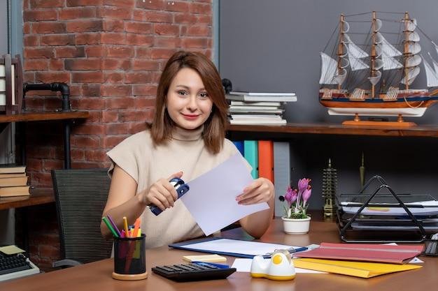 Vooraanzicht blije vrouw die nietmachine gebruikt die aan het bureau in kantoor zit