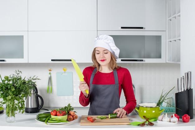 Vooraanzicht blije vrouwelijke kok in schort met mes