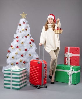 Vooraanzicht blond meisje met kerstmuts met mand met xmas speelgoed