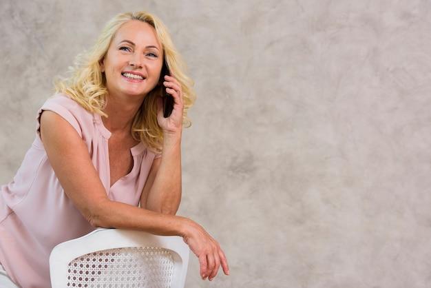 Vooraanzicht blonde dame praten aan de telefoon met kopie ruimte