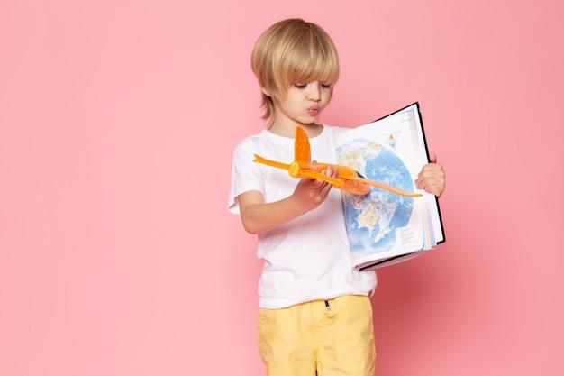 Vooraanzicht blonde jongen schattig schattig in wit t-shirt op de roze vloer