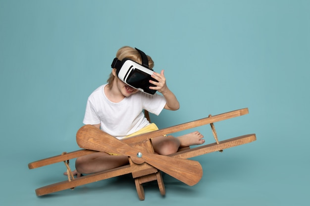 Vooraanzicht blonde jongen spelen vr bril in wit t-shirt op het blauwe bureau