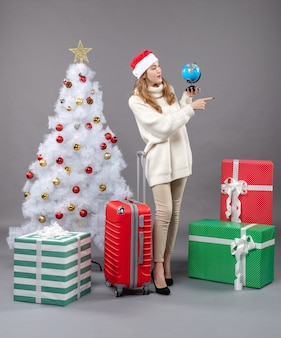 Vooraanzicht blonde kerst vrouw met kerstmuts kijken naar globe