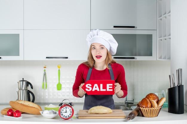 Vooraanzicht blonde mooie vrouw in kok hoed en schort met verkoop teken in de keuken