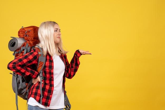 Vooraanzicht blonde reiziger vrouw met haar rugzak hand op een taille te zetten