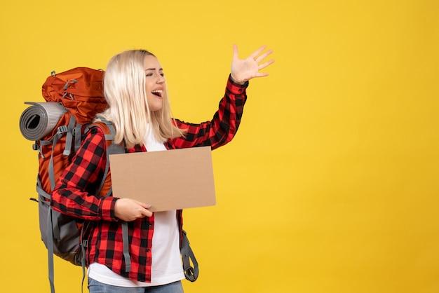 Vooraanzicht blonde reiziger vrouw met haar rugzak met kartonnen lift