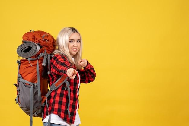 Vooraanzicht blonde reiziger vrouw met haar rugzak wijzende vinger voorzijde