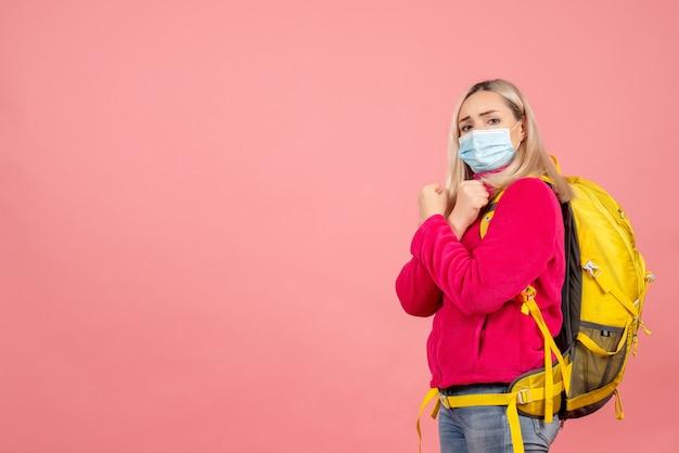 Vooraanzicht blonde reizigersvrouw met gele rugzak die masker draagt dat handen kruist