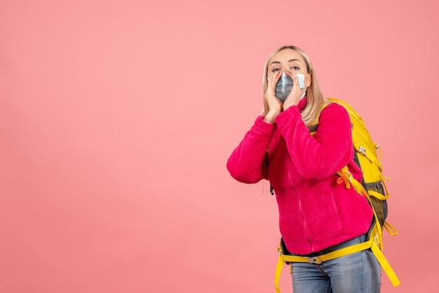 Vooraanzicht blonde reizigersvrouw met gele rugzak die masker draagt dat iemand roept