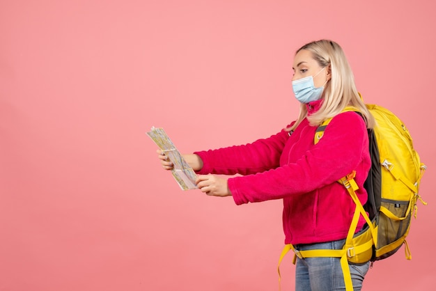Vooraanzicht blonde reizigersvrouw met gele rugzak die masker dragen die kaart bekijken