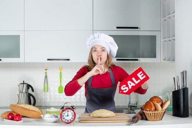 Vooraanzicht blonde vrouw in koksmuts en schort met verkoopbord waardoor stilte in de keuken zingt
