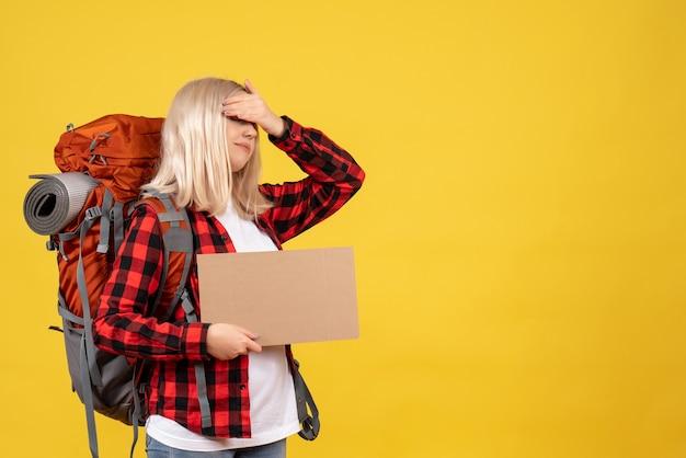 Vooraanzicht blonde vrouw met haar rugzak hand op haar ogen met karton te zetten