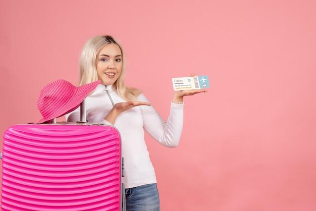 Vooraanzicht blonde vrouw met roze koffer met vliegticket