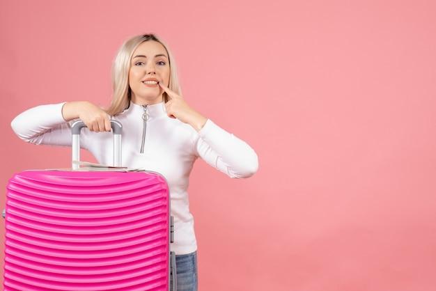 Vooraanzicht blonde vrouw met roze koffer wijzend op haar glimlach