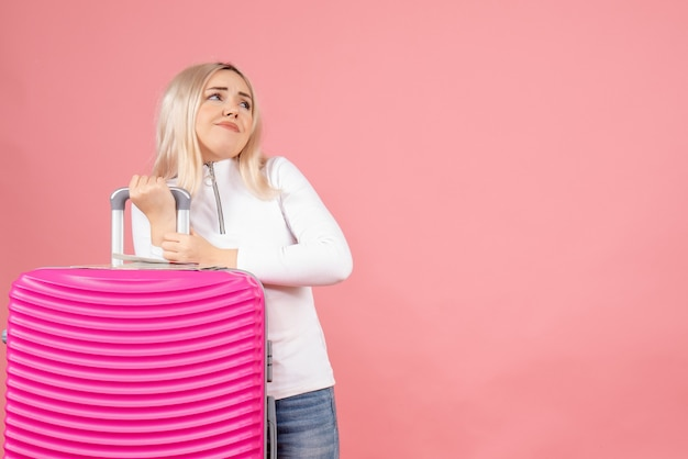 Vooraanzicht blonde vrouw met roze koffer