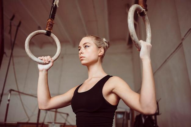 Vooraanzicht blonde vrouw training op gymnastiek ringen