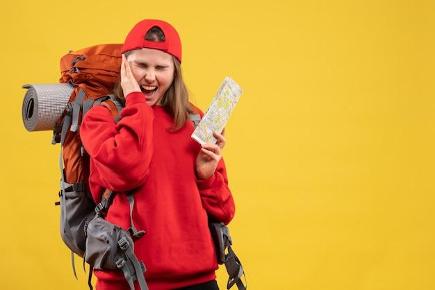 Vooraanzicht boos vrouwelijke backpacker houden reiskaart met haar oor