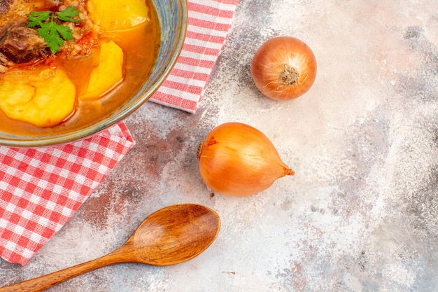Vooraanzicht bozbash soep keukenhanddoek een houten lepel uien op naakte achtergrond azerbeidzjaanse keuken