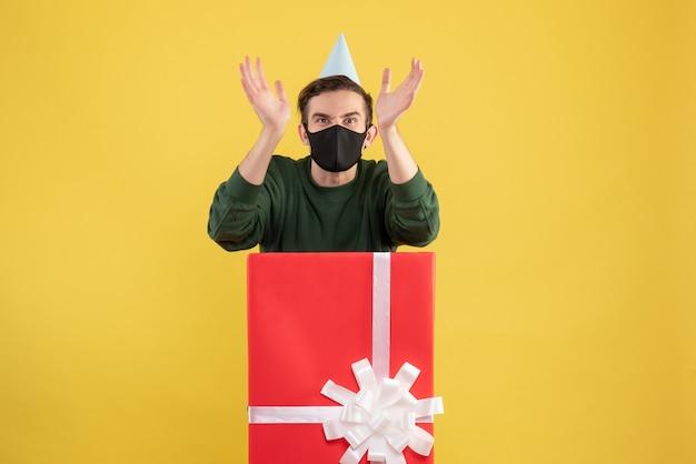 Vooraanzicht boze jonge man met feestpet en masker staande achter grote geschenkdoos op geel