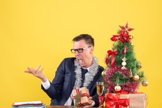 Vooraanzicht boze man met bril zittend aan de tafel in de buurt van kerstboom en presenteert op gele achtergrond