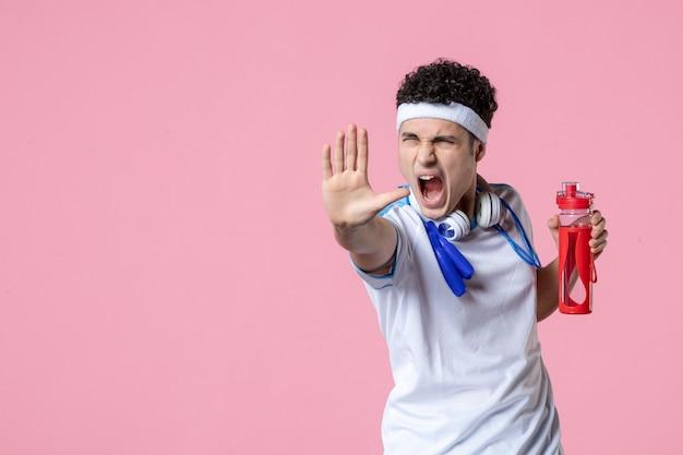 Vooraanzicht boze mannelijke atleet in sportkleren met fles water