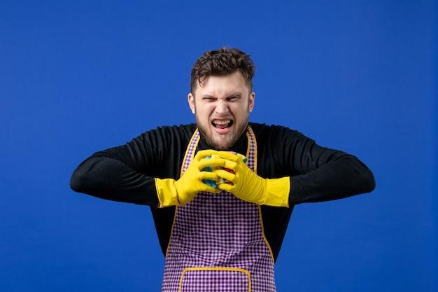 Vooraanzicht boze mannelijke huishoudster knijp sponzen op blauwe geïsoleerde ruimte
