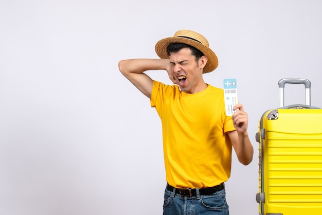 Vooraanzicht boze toerist in gele t-shirt die zich dichtbij het gele kaartje van de kofferholding bevindt