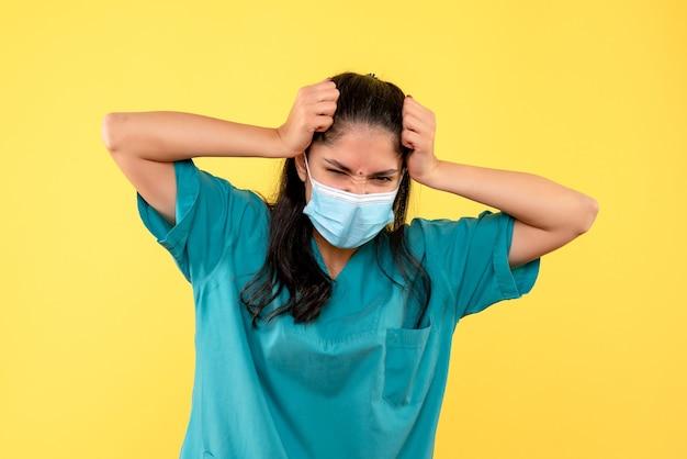 Vooraanzicht boze vrouwelijke arts die haar hoofd houdt dat zich op gele achtergrond bevindt