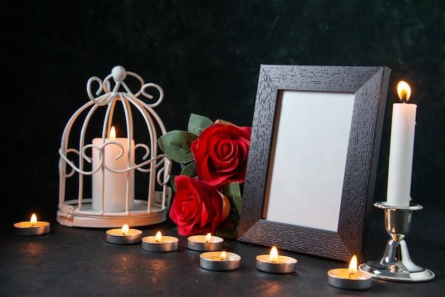 Vooraanzicht brandende kaarsen met fotolijst als geheugen voor gevallen donker oppervlak