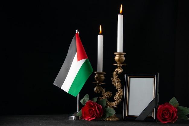 Vooraanzicht brandende kaarsen met palestijnse vlag en fotolijst donker oppervlak