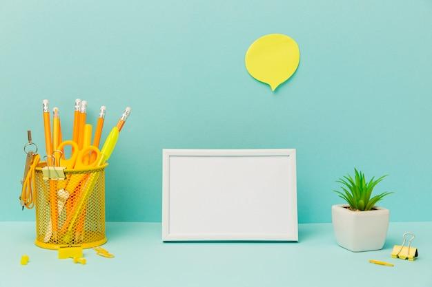 Vooraanzicht briefpapier objecten met frame en plant