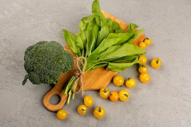 Vooraanzicht broccoli groene bladeren samen met gele tomaten op de grijze achtergrond