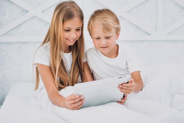 Vooraanzicht broers en zussen in bed blijven tijdens het spelen op een tablet