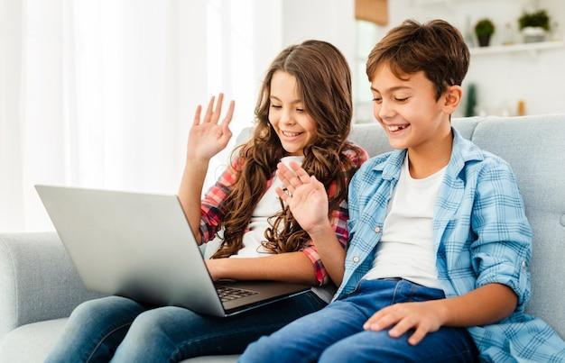 Vooraanzicht broers en zussen thuis met behulp van laptop