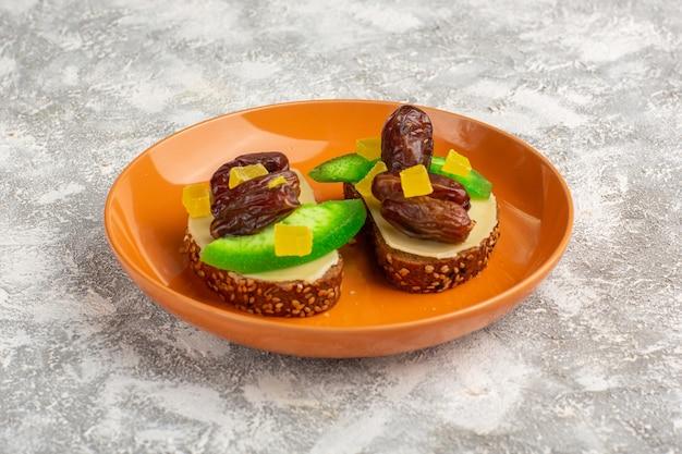 Vooraanzicht brood toast met komkommer en gedroogde pruimen binnen oranje plaat op wit oppervlak