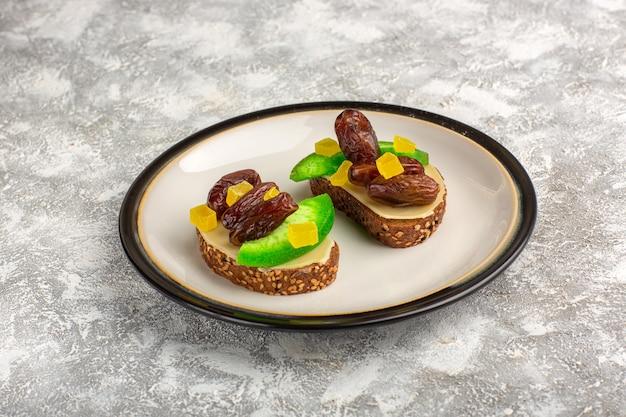Vooraanzicht brood toast met komkommer en gedroogde pruimen binnen plaat op wit oppervlak