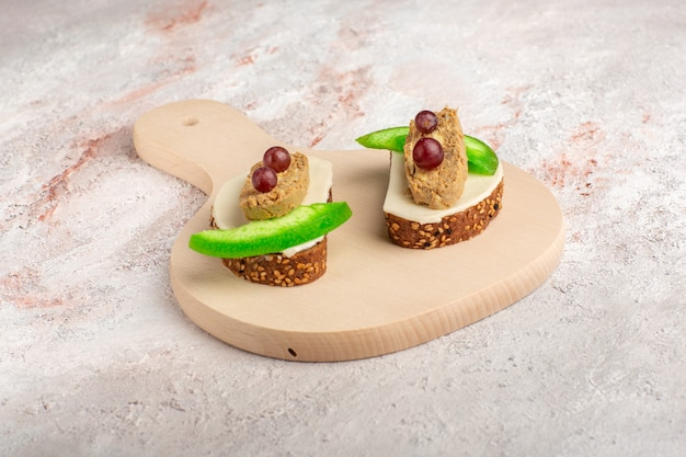 Vooraanzicht brood toast met paté en plakjes komkommer binnen plaat op wit oppervlak