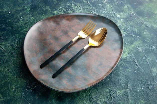 Vooraanzicht bruine lege plaat met gouden lepel en vork op donkere achtergrond
