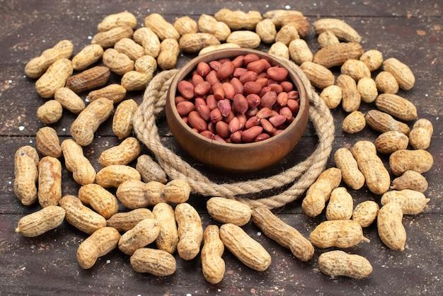 Vooraanzicht bruine rauwe noten in ronde kom met touwen en gele noten op het bruine achtergrond noten walnoot snack zout