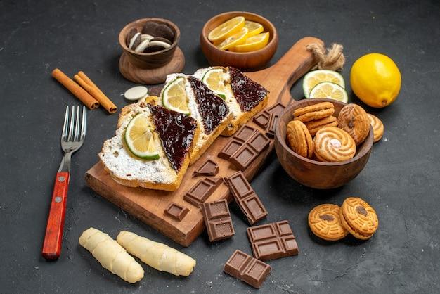 Vooraanzicht cakeplakken met chocolade en koekjes op donkere achtergrond