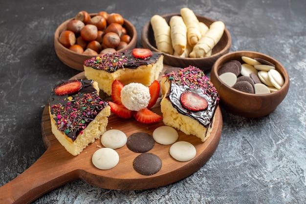 Vooraanzicht cakeplakken met noten en koekjes op donkere achtergrond