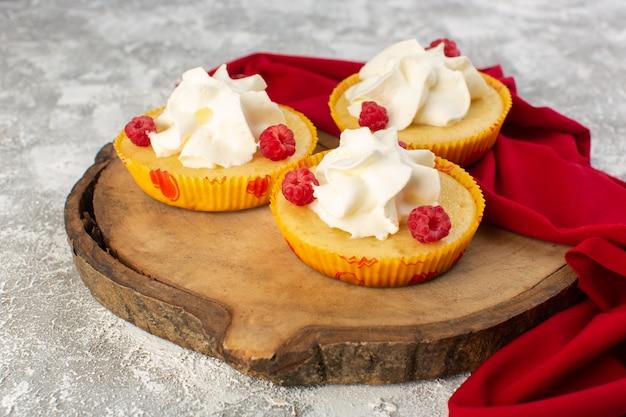 Vooraanzicht cakes met crème lekker gebakken ontworpen met frambozen op het grijze oppervlak