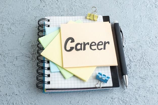 Vooraanzicht carrière geschreven notitie met stickers en blocnote op witte achtergrond