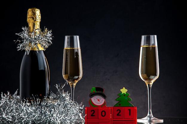 Vooraanzicht champagne in fles en glazen houtblokken op donkere ondergrond