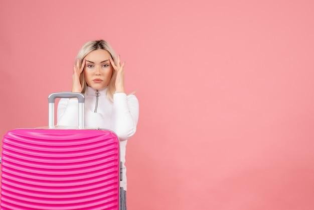 Vooraanzicht charmante blonde vrouw met roze koffer vingers in de buurt van de ogen