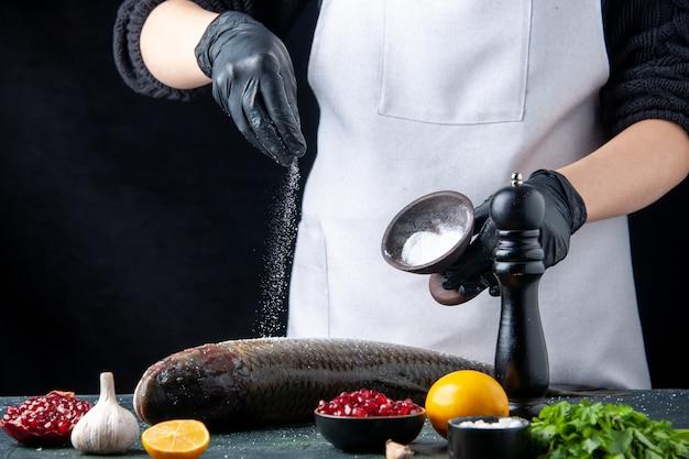 Vooraanzicht chef-kok in schort besprenkeld zout op verse vis granaatappel zaden in kom op tafel