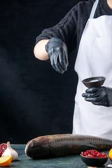 Vooraanzicht chef-kok in witte schort besprenkeld zout op verse vis granaatappel zaden in kom knoflook op tafel