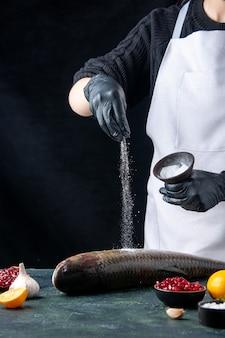 Vooraanzicht chef-kok in witte schort besprenkeld zout op verse vis granaatappel zaden in kom op tafel