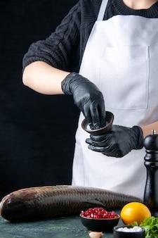 Vooraanzicht chef-kok in witte schort besprenkeld zout op verse vis granaatappel zaden in kom pepermolen op tafel